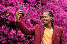 Trendy Black Man With Smartphone Taking Photo Against Blooming Tree