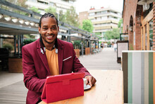 Stylish Ethnic Man With Tablet And Coffee In Street Cafe