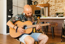 Bearded Musician Playing Guitar At Home