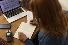 Unrecognizable Woman Writing In Notebook Before Recording Podcast