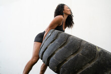 Strong Ethnic Sportswoman Flipping Tire During Workout