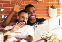 Multiethnic Gay Couple Having Video Conversation On Tablet