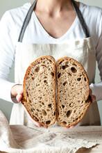Hands Holding Freshly Baked Sourdough Bread