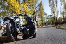 Focused Aged Male Biker Checking Motorcycle On Road In Countryside