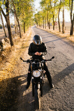 Focused Mature Male Biker Preparing For Riding In Sunny Day