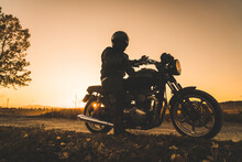 Unrecognizable Racer Driving Motorbike In Sunset In Rural Location