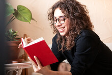 Young Smiling Woman In Eyeglasses Reading Book