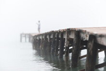 Unrecognizable Person On Wooden Quay In Foggy Morning
