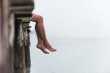 Crop Woman Sitting On Pier In Foggy Morning