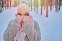 A Smiling Woman Wraps Herself In Clothes Warming Up In A Winter Forest With Trees In The Snow