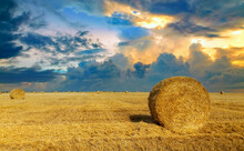 Beautiful Sunset Over Farm Field With Many Hay Bales With Blue Sky And Colorful Clouds In Background.