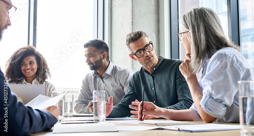 Diverse business people partners group negotiating at boardroom meeting.Multiethnic executive team discussing financial partnership agreement project strategy brainstorming sitting at table in office.
