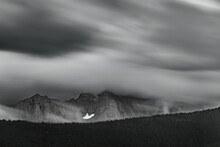 FAST MOVING WIND DRIVEN CLOUDS OVER MOUNTAINS AND PINES IN B&W - GLACIER NP.