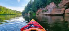 Canoeing In Summer With Beautiful Blue Skies In A River With A Forest.