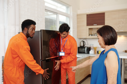 Canvas Print Senior woman telling movers where to put new big refrigerator in her kitchen
