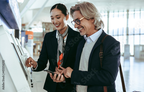 Ground attendant helping business traveler in self check in