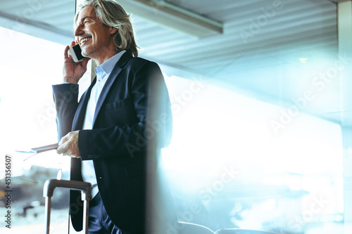 Businessman at airport waiting lounge talking on phone