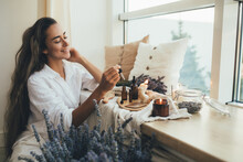 Young Woman Applying Natural Organic Essential Oil On Hair And Skin. Home Spa And Beauty Rituals.