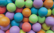 Background From Multicolored Bright Small Wooden Balls Of Blue, Yellow, Red, Lilac And Green Colors