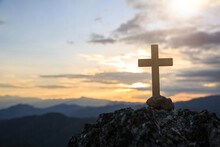 Jesus Christ Cross. Easter, Resurrection Concept. Christian Wooden Cross On A Background With Dramatic Lighting, Colorful Mountain Sunset.