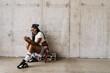 Leinwandbild Motiv Black young woman using mobile phone while sitting on tape recorder