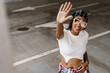 Leinwandbild Motiv Black young woman smiling and gesturing while posing on parking