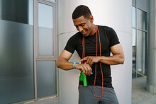 Black Sportsman Using Smartwatch While Working Out With Jumping Rope