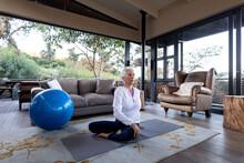 Senior Caucasian Woman In Living Room Exercising, Sitting On The Floor