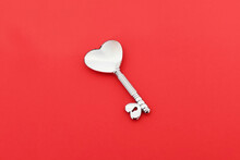 Silver Heart Shaped Key On Red Background