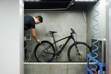 Man Cleaning Gear Cassette Of Bike Wheel