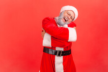 Elderly Man With Gray Beard Wearing Santa Claus Costume Hugging Himself, Feeling Comfortable, Narcissistic Egoistic Person, Happy Expression. Indoor Studio Shot Isolated On Red Background.