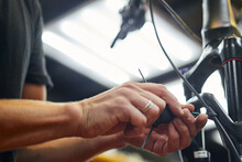 Mechanic Fixing Brake Cable Of Bicycle In Garage