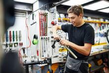 Smiling Man Repairing Bicycle Fork In Garage