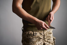 Mid-section Shot Of A Military Man Sharpening His Pocket Knife