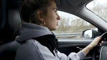 Young Woman With Natural Look Driving A Passenger Car On A German Highway. The Young Woman Shows Various Emotional Reactions To The Traffic Event.