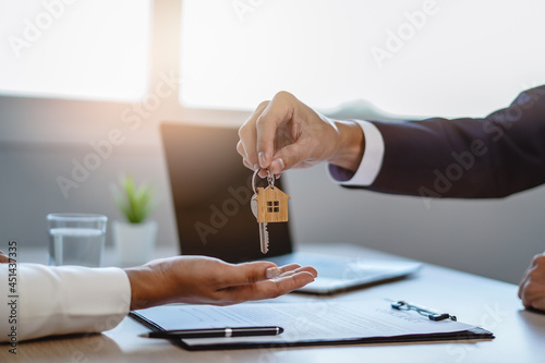 Fotografie, Obraz close up view hand of property realtor / landlord giving key house to buyer / tenant