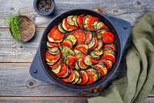 Modern Style Traditional French Ratatouille With Tomatoes, Eggplant And Zucchini Served As Top View In A Rustic Cast-iron Skillet
