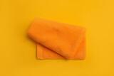 Fototapeta Kawa jest smaczna - Folded orange beach towel on yellow background, top view