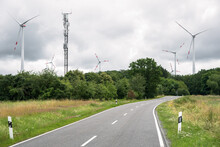 Deserted Country Road Running Through A Wind Farm On A Cloudy Summer Day
