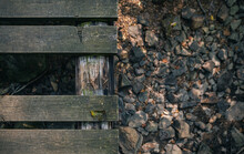 Looking Down At Footbridge With A Board Missing. Dry Creek Bed Stones Underneath. Nature And Hiking Trail Background.