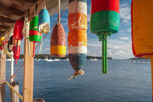 Colorful Working Boat Lobster FloatS Hanging On The Deck Of A Lobster Processing Plant With Lobster Boats In The Background On A Perfect Autumn Day