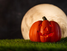 Halloween. On The Green Grass, There Is One Pumpkin With An Eerie Smile Against The Background Of The Dark Night Sky And The White Moon. Traditional Autumn Holiday. Advertising, Postcard.