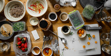 A Table On Which Products For Cooking And Decorating Dishes Prepared For A Photo Shoot Are Arranged In A Chaotic Manner. Copy Space