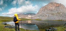 An Explorer With Yellow Outdoor Jacket And Backpack Observes The Mountainous Area And High Elevation Lake.