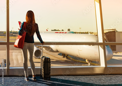 COVID-19 Vaccine passport for travel woman standing with suitcase watching airport window. Tourist waiting at terminal to board before departure. Travel coronavirus lifestyle