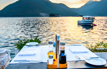 Restaurant Table Laid Out Awaiting Customers At Sunset By The Waterside,Perast,Montenegro.