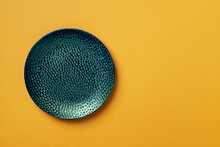 Textured Turquoise Teal Round Plate On A Yellow Textured Background. Modern Ceramic Crockery And Tableware For Stylish Food Design. Empty Dishes. Copy Space.