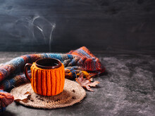 Hot Cup Of Coffee In An Orange Jacket And A Knitted Autumn Colorful Scarf, Autumn Maple Leaves