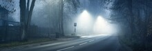 An Empty Illuminated Motorway Through Deciduous Forest In A Morning Fog, Lanterns Close-up. Bus Stop In The Background. Latvia