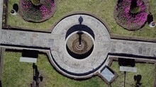 Small Beautiful Fountain With Pink Flower Bushes In City Surroundings, Drone Ascend View